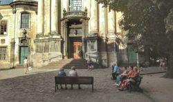 Bătrâni așteptând în tihnă vecernia, la umbra oferită generos, de copacii din fața unei biserici greco-catolice din vechiul centru istoric al orașului
